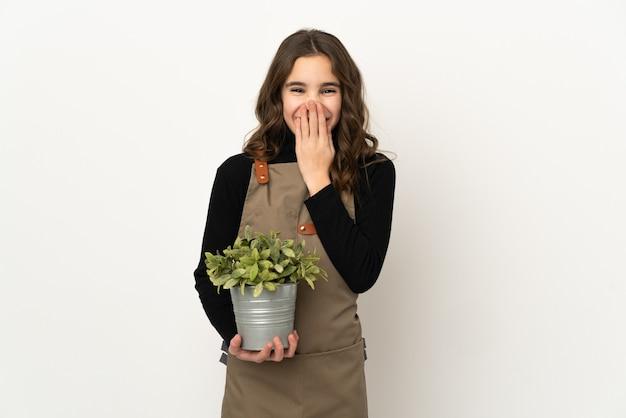Bambina che tiene una pianta isolata bocca di copertura felice e sorridente con la mano