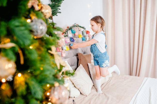 Bambina che tiene il calendario dell'avvento fatto a mano della scatola presente a casa. calendario dell'avvento natalizio fai da te per bambini