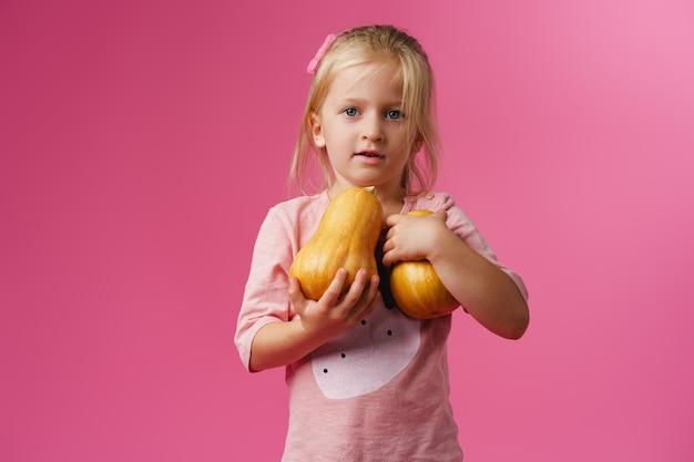 Bambina che tiene la zucca nelle sue mani su sfondo rosa pastello