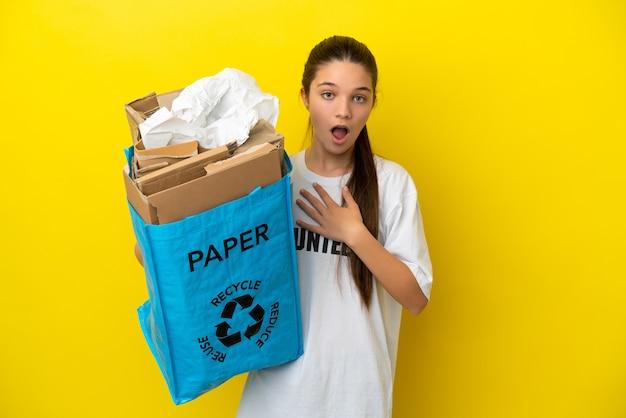 Bambina che tiene in mano un sacchetto per il riciclaggio pieno di carta da riciclare su uno sfondo giallo isolato sorpreso e scioccato mentre guarda a destra
