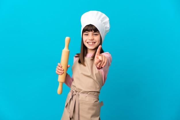 Bambina che tiene un mattarello isolato su sfondo blu che mostra e alzando un dito