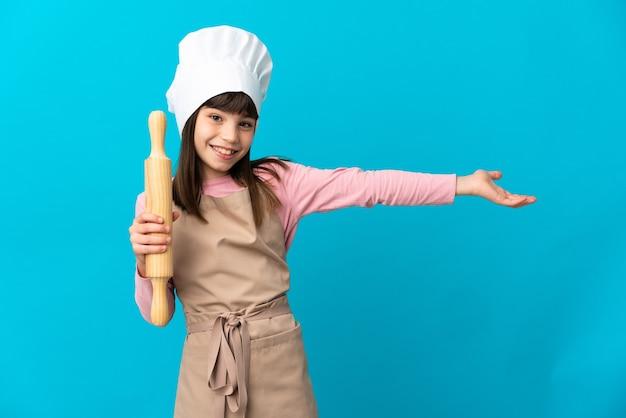Bambina che tiene un mattarello isolato sulla parete blu che estende le mani a lato per invitare a venire