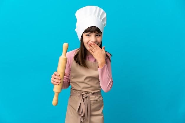 Bambina che tiene un mattarello isolato sulla parete blu felice e sorridente che copre la bocca con la mano