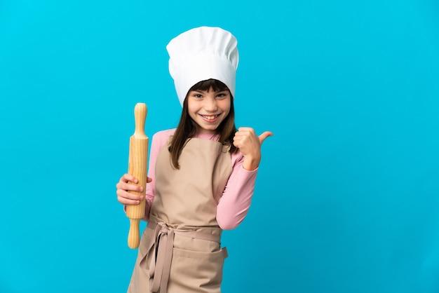 Bambina che tiene un mattarello isolato sulla parete blu che punta di lato per presentare un prodotto