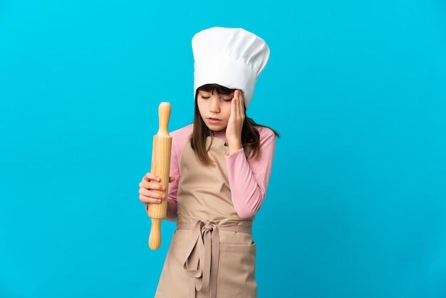 Bambina che tiene un mattarello isolato sulla parete blu con mal di testa