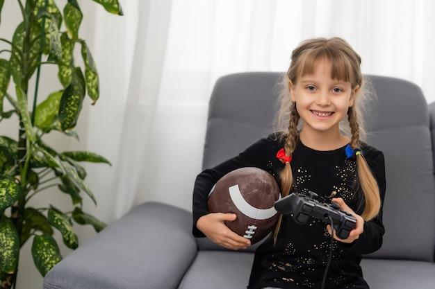 Bambina che tiene una palla da rugby e un joystick per giocare ai videogiochi