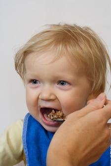 Bambina che tiene un cucchiaio tra le braccia e mangia un pap