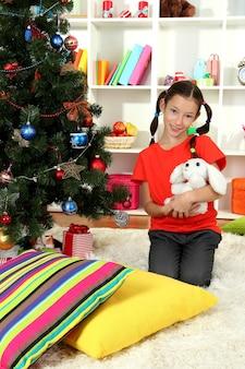 Bambina che tiene il giocattolo vicino all'albero di natale