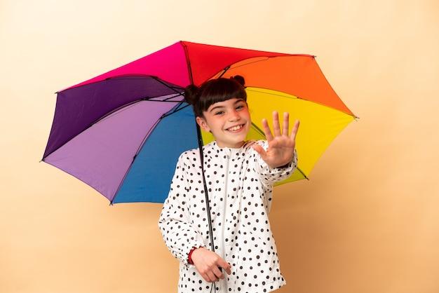 Bambina che tiene un ombrello isolato sul beige contando cinque con le dita