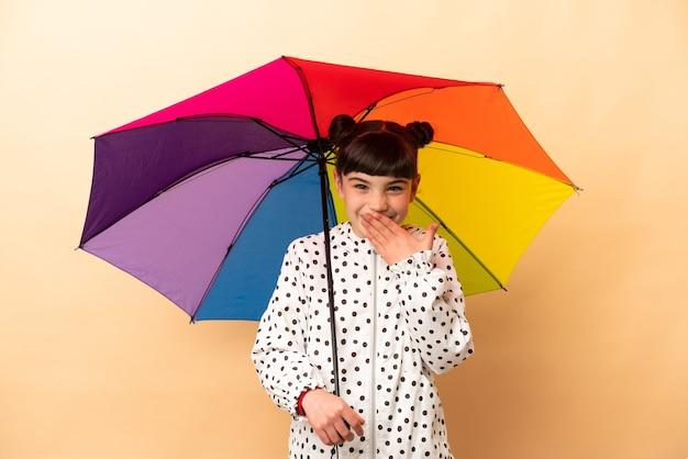 Bambina che tiene un ombrello isolato sulla bocca coning felice e sorridente beige con la mano