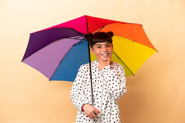 Bambina che tiene un ombrello isolato su beige felice e sorridente
