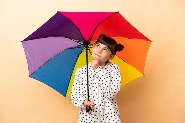 Bambina che tiene un ombrello isolato su beige e alzando lo sguardo