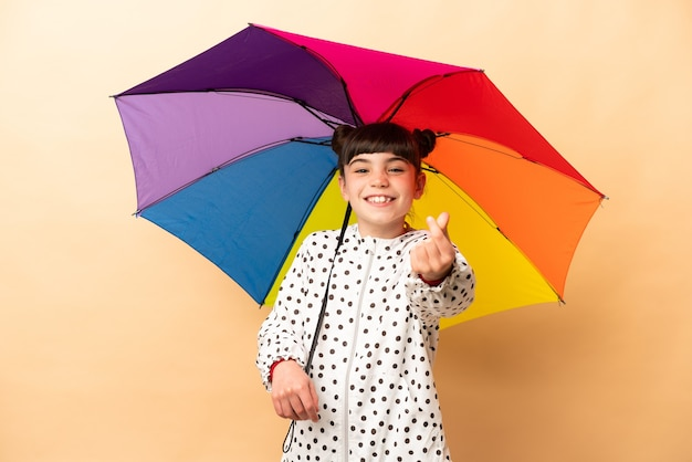 Bambina che tiene un ombrello isolato su beige che fa gesto di soldi