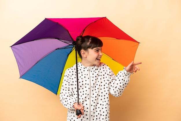 Bambina che tiene un ombrello isolato sul dito puntato beige a lato e che presenta un prodotto
