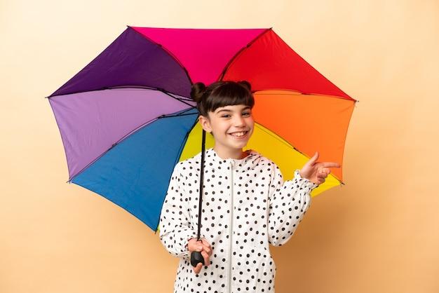 Bambina che tiene un ombrello isolato sul dito puntato beige a lato