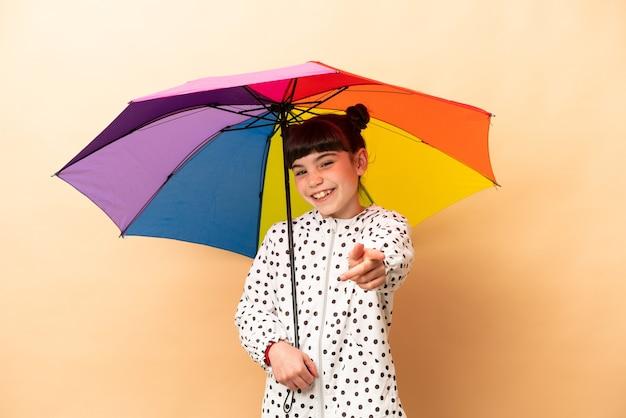 Bambina che tiene un ombrello isolato sulla parte anteriore di puntamento beige con felice espressione