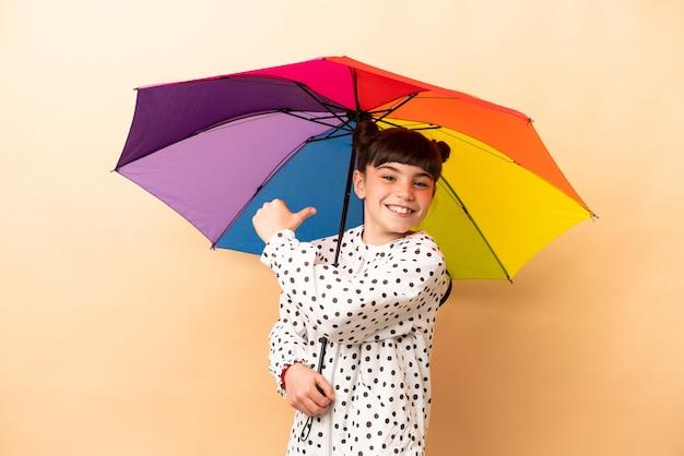 Bambina che tiene un ombrello isolato su beige orgoglioso e soddisfatto di sé