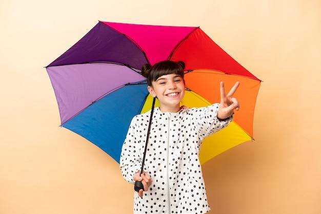 Bambina che tiene un ombrello isolato sul beige che sorride e che mostra il segno di vittoria