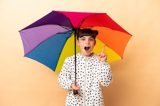 Bambina che tiene un ombrello isolato sul beige pensando un'idea puntando il dito verso l'alto