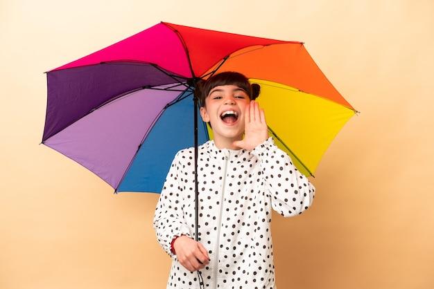 Bambina che tiene un ombrello isolato sulla parete beige che grida con la bocca spalancata