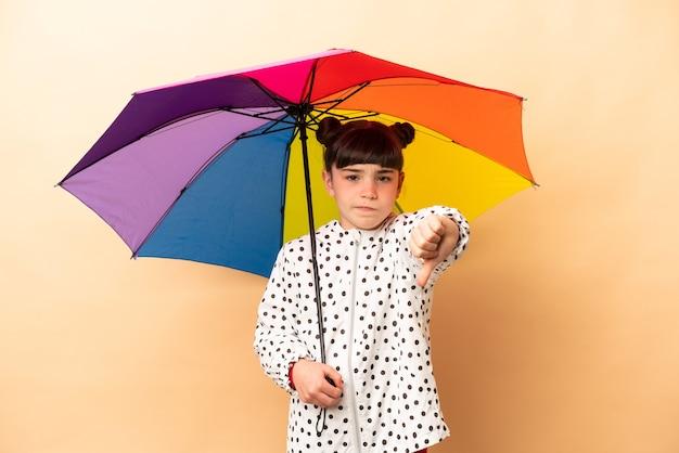Bambina che tiene un ombrello isolato sul muro beige che mostra il pollice verso il basso con espressione negativa