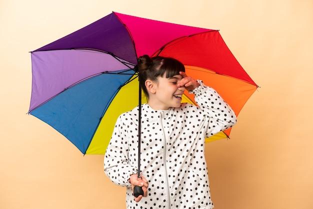 Bambina che tiene un ombrello isolato sulla parete beige che sorride molto