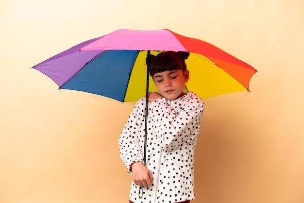 Bambina che tiene un ombrello isolato sul muro beige soffre di dolore alla spalla per aver fatto uno sforzo