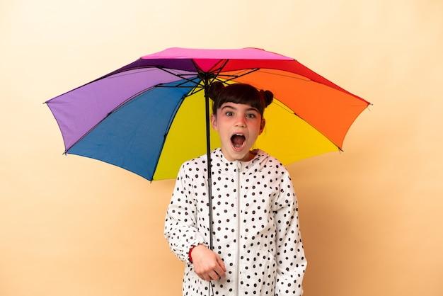 Bambina che tiene un ombrello isolato sulla parete beige con l'espressione facciale di sorpresa