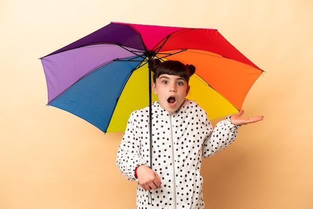 Bambina che tiene un ombrello isolato sul beige con l'espressione facciale scioccata