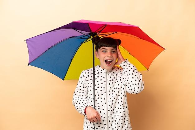Bambina che tiene un ombrello isolato sul beige con espressione di sorpresa