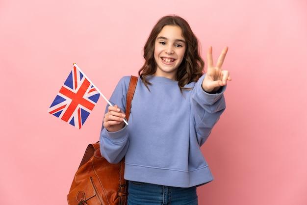 Bambina che tiene una bandiera del regno unito isolata su sfondo rosa sorridendo e mostrando il segno di vittoria