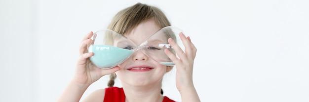 La bambina tiene in mano la clessidra blu. pianificare il concetto di tempo dei bambini