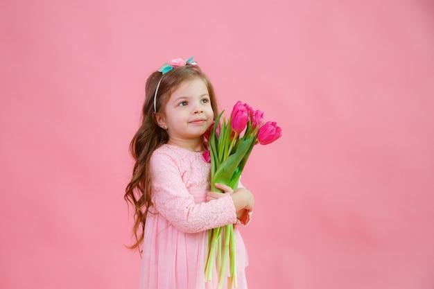 La bambina tiene un mazzo di tulipani su uno sfondo rosa