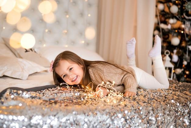 Una bambina a casa sullo sfondo di un albero di natale. ritratto sul letto