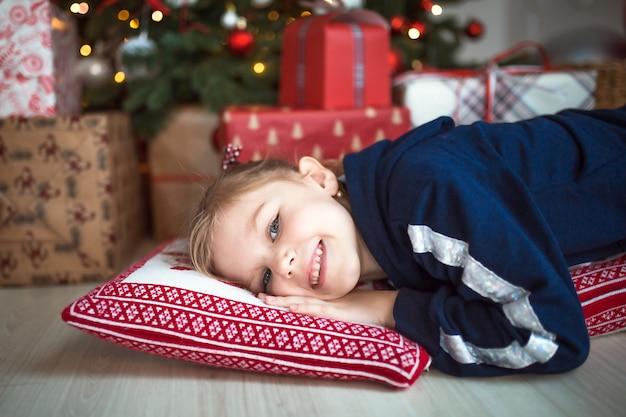 Una bambina in abiti domestici è sdraiata sotto l'albero di natale vicino alle scatole con i regali