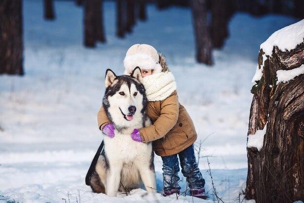 Bambina che abbraccia il suo grosso cane malamute
