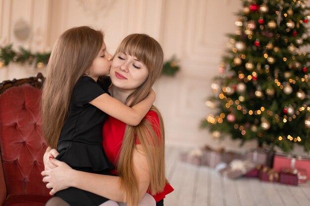 La bambina abbraccia la sua mamma vicino all'albero di natale. momenti gioiosi di un'infanzia felice.