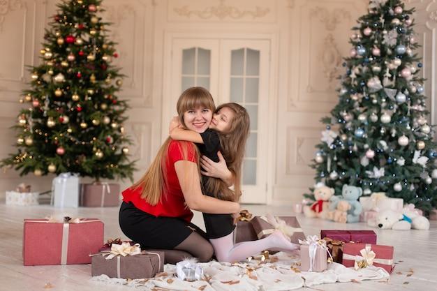 La bambina abbraccia la sua mamma vicino all'albero di natale