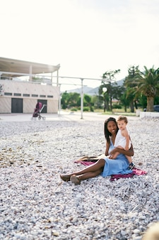 La bambina abbraccia la mamma seduta sulla spiaggia