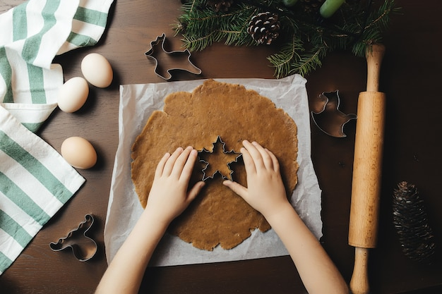 La bambina sta cuocendo i biscotti del pan di zenzero di natale.