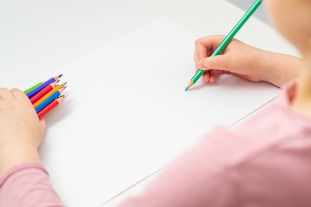 La bambina sta disegnando con una matita verde su un foglio di carta bianco che tiene in mano un mazzo di matite colorate. messa a fuoco selettiva.