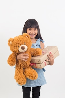 La bambina sta abbracciando un orsacchiotto con confezione regalo