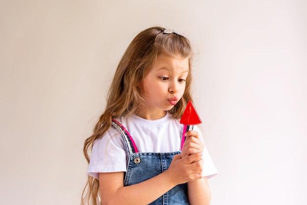 Una bambina sta guardando un lecca-lecca.