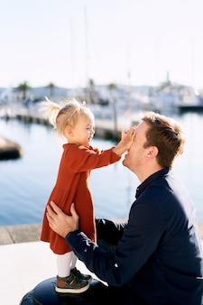 La bambina sta giocando a peek-a-boo con il suo papà su un porticciolo.