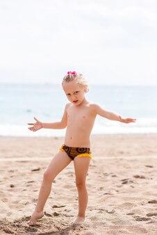 La bambina sta giocando nella sabbia in riva al mare.