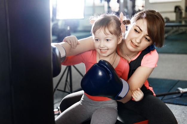 La bambina pratica la boxe, la ragazza insegna alla mamma a boxare, divertente madre e figlia in palestra, felice madre e figlia in palestra