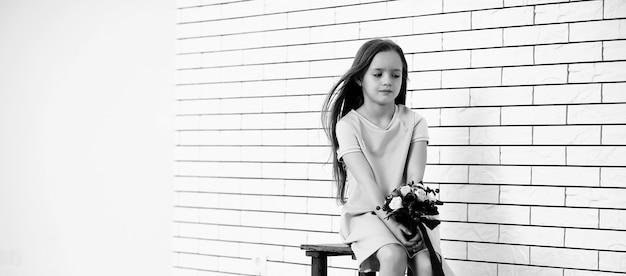 La bambina è seduta su una sedia e posa sulla telecamera