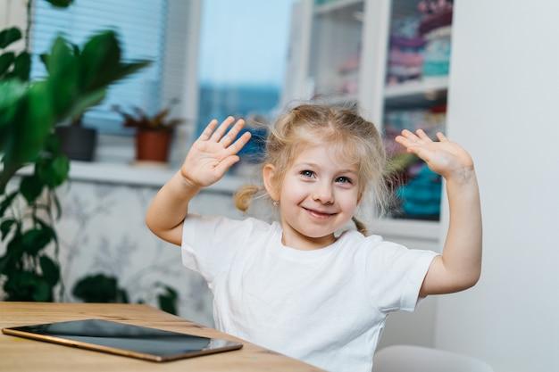Una bambina è seduta a un tavolo con una tavoletta con le mani alzate in aria sorridente e felice, sperimentando la felicità.