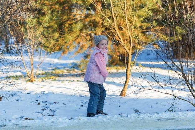 La bambina sta sorridendo nella foresta di inverno. infanzia felice. bambini all'aperto divertimento invernale concetto di vacanza