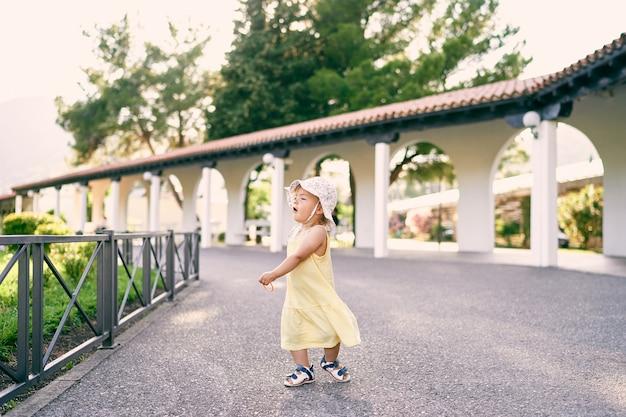 La bambina gira sul sentiero di ghiaia vicino al gazebo nel parco